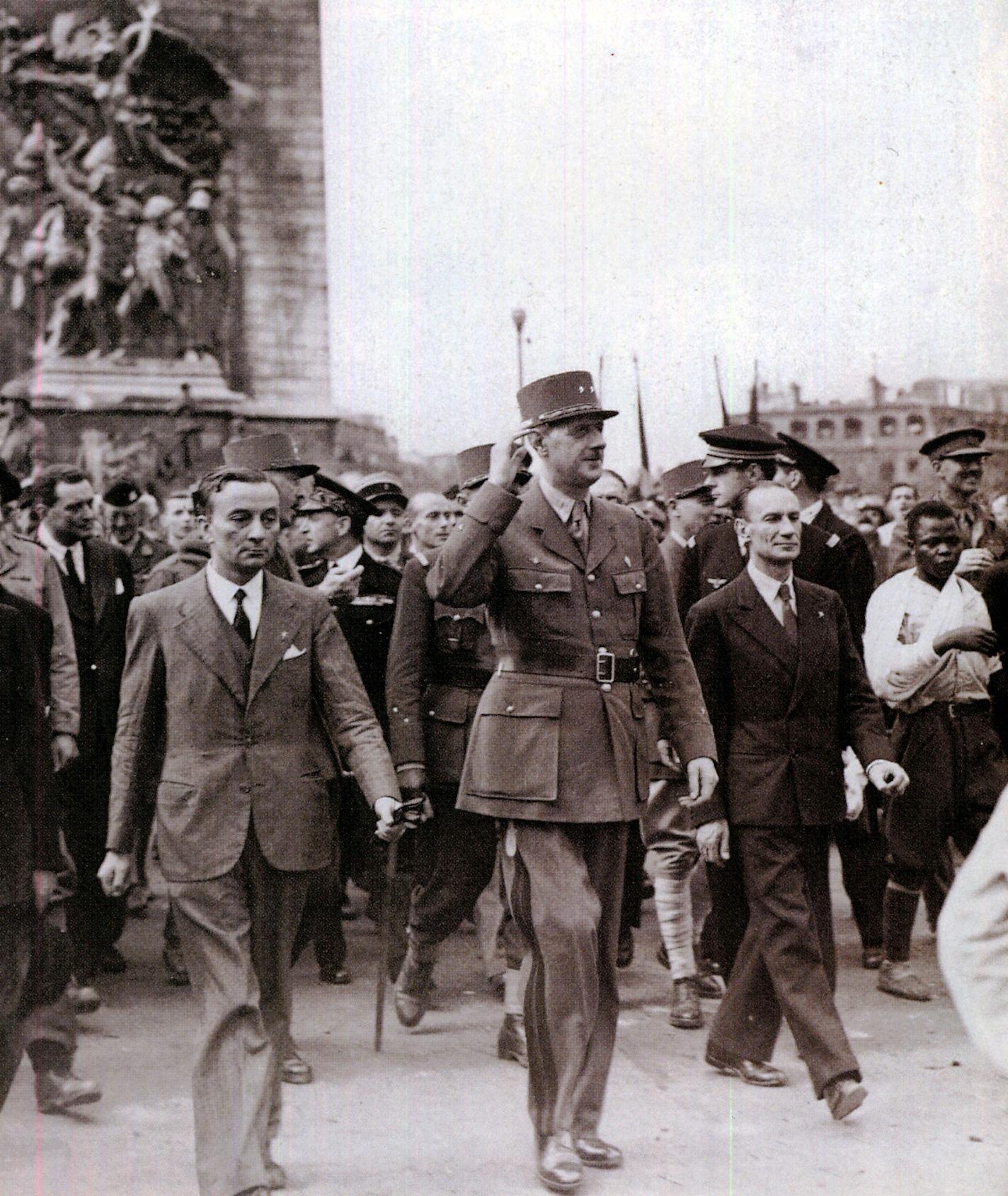 Le général de Gaulle accompagné de Georges Bidault (à gauche) et Alexandre Parodi (à droite) descend les Champs-Elysées. A droite on aperçoit Georges Dukson.